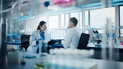 Modern Medical Research Laboratory: Portrait of Two Scientists Working, Using Digital Tablet, Analyzing Samples, Talking. Advanced Scientific Pharmaceutical Lab for Medicine, Biotechnology Development