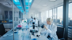 Modern Medical Research Laboratory: Team of Scientists Working with Pipette, Analysing Microbiological Sample, Talking. Advanced Scientific Lab for Drugs, Microbiology Development. High-Tech Equipment