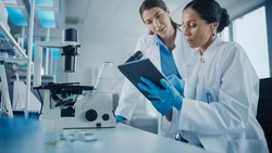 Modern Medical Research Laboratory: Two Female Scientists Working, Using Digital Tablet, Analysing Samples, Talking. Advanced Scientific Pharmaceutical Lab for Medicine, Biotechnology Development