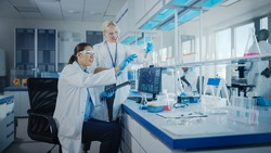 Modern Medical Research Laboratory: Two Female Scientists Working Using Digital Tablet, Analysing Biochemicals Samples. Scientific Lab for Medicine, Microbiology Development. Advanced Equipment