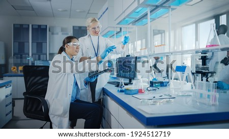 Modern Medical Research Laboratory: Two Female Scientists Working Using Digital Tablet, Analysing Biochemicals Samples. Scientific Lab for Medicine, Microbiology Development. Advanced Equipment Foto stock ©