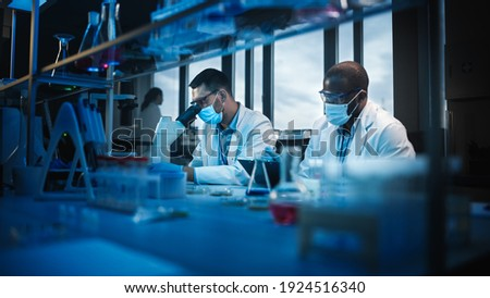 Modern Medical Research Laboratory: Two Scientists Wearing Face Masks use Microscope, Analyse Sample in Petri Dish, Talk. Advanced Scientific Lab for Medicine, Biotechnology. Blue Color