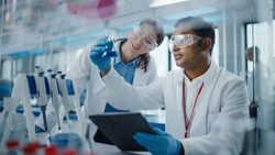 Modern Medical Research Laboratory: Two Scientists Working Together Analysing Chemicals in Laboratory Flask, Discussing Problem. Advanced Scientific Lab for Medicine, Biotechnology, Molecular Biology