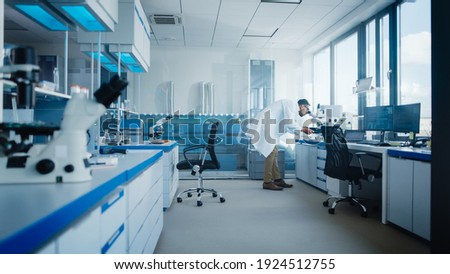 Modern Medical Research Laboratory with Male Scientist Looking Under Microscope, Analysing Microbiological Sample. Advanced Scientific Lab for Drugs, Vaccine Development, Full of High-Tech Equipment