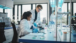 Modern Medicine Laboratory: Diverse Team of Multi-Ethnic Young Scientists Analysing Test Samples. Advanced Lab with High-Tech Equipment, Microbiology Researchers Design, Develop Drugs, Doing Research