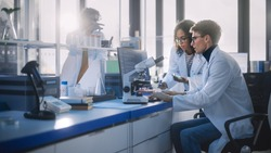 Modern Medicine Research Laboratory: Diverse Team of Multi-Ethnic Young Scientists Analysing Test Samples. Advanced Lab with High-Tech Equipment, Microbiology Researchers Design, Develop Drugs