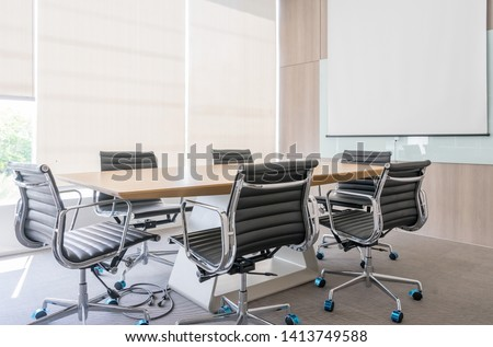 Modern meeting room with projection screen and conference table #1413749588
