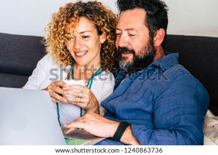 Modern middle age 40s couple on internet with laptop sitting on the couch at home while search and use web technology for work or shopping online - people together with computer concept Stock photo ©