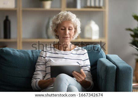 Modern middle-aged 50s grandmother sit relax on couch in living room using tablet, contemporary elderly mature woman rest on sofa at home browse Internet on pad, old people technology concept
