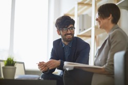 Modern middle eastern man wearing creative haircut and glasses  communicating with  his colleague  in modern office, both smiling looking happy