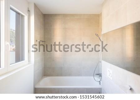 Modern minimal bathroom with large tile bathtub. Nobody inside