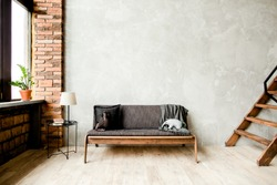 Modern minimalist interior with a sofa on an empty wall in the living room. Loft style