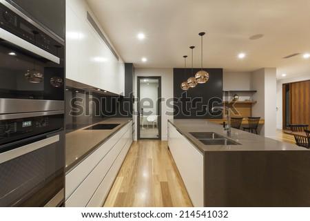 Modern minimalist kitchen and living room at night