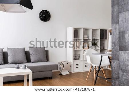 Modern,minimalist living room with resting space, racks and desk corner