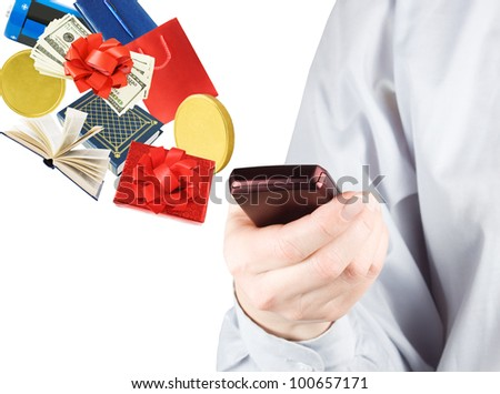 Modern mobile phone in the hand with lots of goods and money isolated on white (e-business concept)