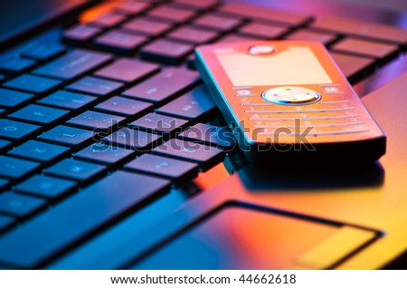 modern mobile phone on laptop keyboard in mixed light