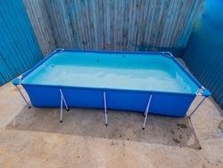Modern model of carcass pool for children in country house on flat concreted plot. Sunny day of summer.