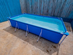 Modern model of carcass swimming pool for children in country house on flat concreted plot. Sunny day of summer.