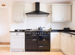 Modern modular kitchen interior in black and off white, with range cooker and chimney extractor hood. UK painted wood farmhouse kitchen design.