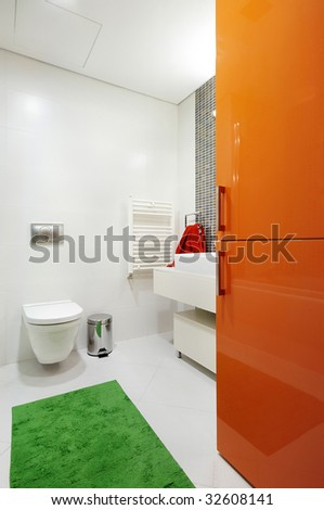 Modern, mostly white bathroom with colorful orange, red, and green accents. Modern toilet and sink basin with a fun bright green rug and bright orange cabinet doors.