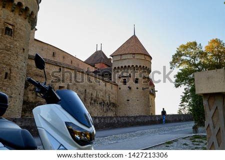 Modern motorcycle in the courtyard of an ancient stone castle. Summer travel concept #1427213306