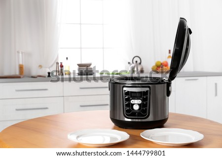 Modern multi cooker and empty plates on table in kitchen Сток-фото ©