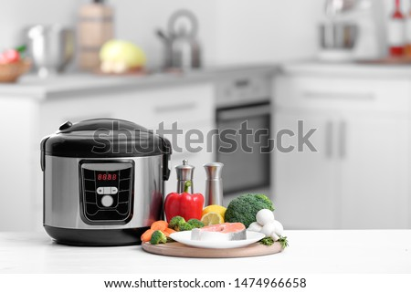 Modern multi cooker and products on table in kitchen. Space for text Stock photo ©