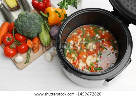 Modern multi cooker and products on white wooden table, above view Stock photo ©