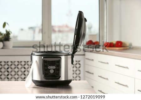 Modern multi cooker on table in kitchen. Space for text