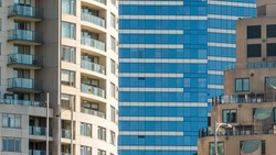 Modern multi-dwelling buildings with  balconies, zoom close up. Apartments in a strata living scheme of common property, offices or commercial buildings.