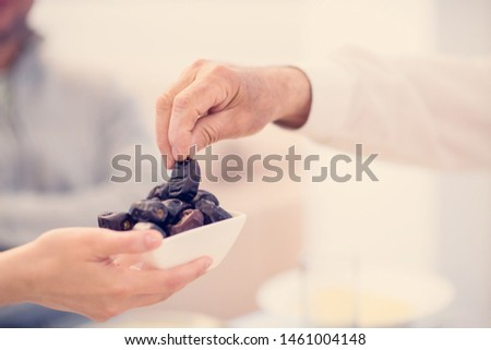 modern multiethnic muslim family sharing a bowl of dates while enjoying iftar dinner together during a ramadan feast at home