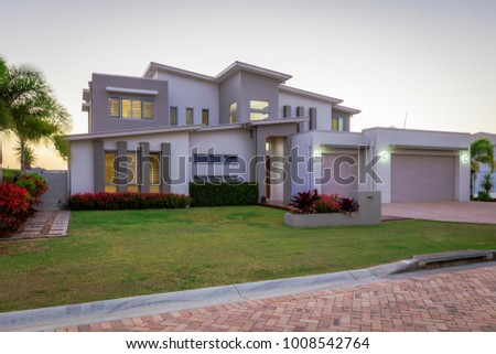 Modern multilevel house exterior at dusk #1008542764