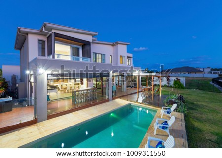 Modern multilevel house exterior with pool at dusk ストックフォト ©