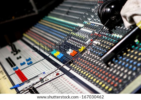 Modern music mixer in audio studio headquarters, dj at stand mixing songs