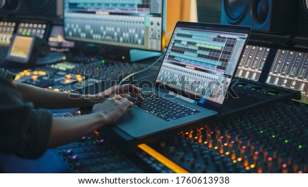 Modern Music Record Studio Control Desk with Laptop Screen Showing User Interface of Digital Audio Workstation Software. Equalizer, Mixer and Professional Equipment. Faders, Sliders. Record. Close-up Zdjęcia stock ©