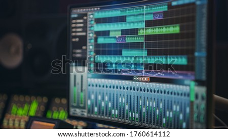 Modern Music Recording Studio Equipment: Computer Screen Showing User Interface of DAW Digital Audio Workstation Software with Track Song Playing. Sound and Music Recording and Editing Application Foto stock ©