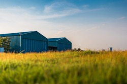 Modern new company warehouse building, farm buildings by the field, outdoors theme concept vintage relaxing.