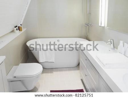 Modern new small bathroom interior with bath tub.