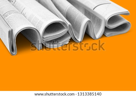 Modern newspapers are folded and composing together the word NEWS, isolated over colored background. Concept of business news, news media, print media and mass media at all. Copy space for your text Foto stock ©