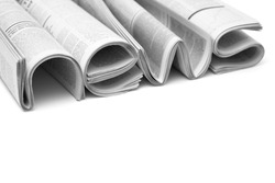 Modern newspapers are folded and composing together the word NEWS, isolated over white background. Concept of business news, news media, print media and mass media at all. Copy space for your text