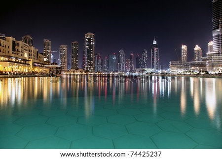 Modern night city of Dubai, with reflection on water surface. - stock photo