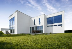 Modern Norwegian design house in concrete white with large windows and green lawn