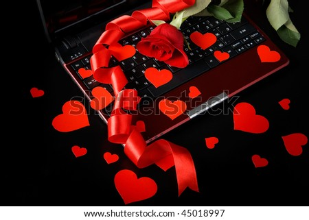 Modern notebook and rose on a black background - stock photo