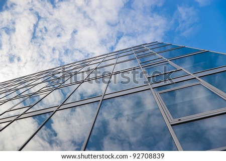 modern office building and sky with clouds reflection