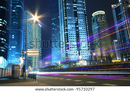 Modern office building background of car night with light trails in Shanghai