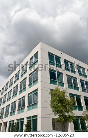 Modern office building in office park with gloomy looming clouds