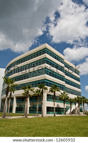 Modern office building in office park with trees and partly cloudy afternoon sky
