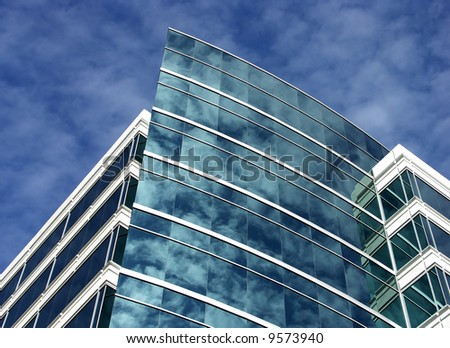 Modern office building with clouds reflected in windows