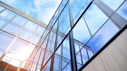 Modern office building with glass facade on a clear sky background. Transparent glass wall of office building.