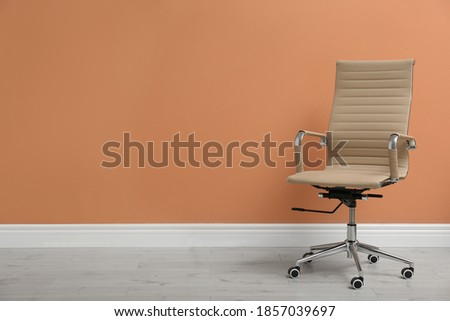 Modern office chair near orange coral wall indoors. Space for text ストックフォト ©